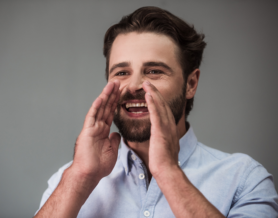 Handsome bearded businessman in smart casual wear is keeping hands near mouth calling someone and smiling on gray background